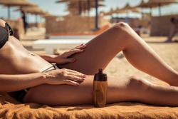 Sensuous slim woman applying suntan lotion oil to her body at the beach