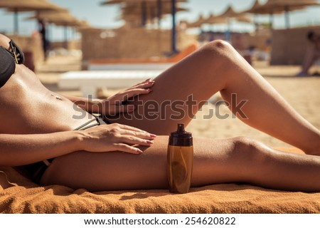 Sensuous slim woman applying suntan lotion oil to her body at the beach Foto d'archivio ©