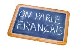 sentence french is spoken written in french on a chalkboard