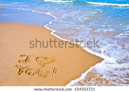 """sentence """"I love you"""" written on the sand of a beach"""