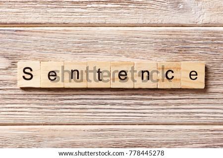 Sentence word written on wood block. Sentence text on table, concept.