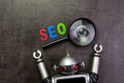 SEO Search engine optimization concept with alphabet abbreviation SEO and globe on magnifying glass and vintage robot.