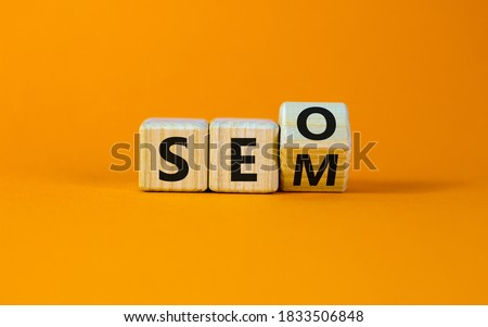 SEO versus SEM. Turned a cube and changed the expression 'SEO' to 'SEM' or vice versa. Concept for Search Engine Optimization and Search Engine Matketing. Beautiful orange background, copy space.