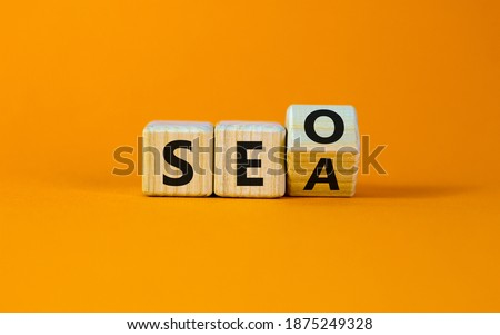 SEO vs SEA. Turned a cube and changed the word 'SEA - search engine advertising' to 'SEO - search engine optimization'. Business and SEO or SEA concept. Beautiful orange background, copy space.