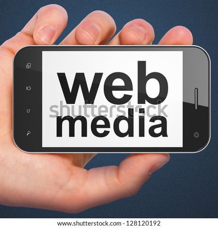 SEO web development concept: hand holding smartphone with word Web Media. Mobile smart phone in hand on Dark Blue background.