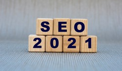 SEO 2021 - word on wooden cubes on a gray background. Business and technology concept