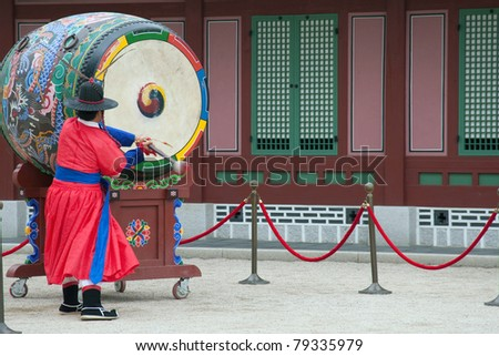 SEOUL - JUNE 09: A palace drummer sounds off for the changing of the guards at the Gyeongbokgong Palace on June 09, 2011 in Seoul, South Korea. This tradition dates back to the Joseon dynasty. - stock photo