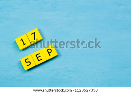 SEP 17, yellow cube calendar on blue wooden surface with copy space