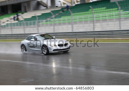 SEPANG - CIRCA MAY 2010: Anonymous BMW car owners test drive their cars at Sepang race track, Malaysia, during a rainy HPC track day circa May 2010.