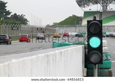 SEPANG - CIRCA MAY 2010: Green traffic light and race cars approach a sharp corner during HPC track day circa May 2010 at Sepang circuit Malaysia.