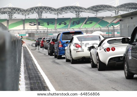 SEPANG - CIRCA MAY 2010:  Numerous cars queue up at the pit lane exit at Sepang Circuit Malaysia, during High Performance Challenge track day event circa May 2010.
