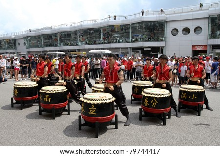SEPANG, MALAYSIA - JUNE 19: Drum troupe playing on Chinese drums entertains visitors at the Supercars Parade event in the Sepang International Circuit on June 19, 2011 in Sepang, Malaysia.