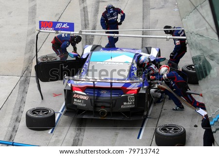SEPANG MALAYSIA JUNE 19 Team Kunimitsu's pit-crew works on the car during pit-stop at the Sepang International Circuit before the Japan SUPER GT Round 3 race on June 19 2011 in Sepang Malaysia
