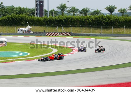 SEPANG, MALAYSIA-MARCH 23 : Three F1 drivers at cornering area in soft motion blur on races during the second practice session on March 23, 2012 in Sepang International Circuit in Sepang, Malaysia.