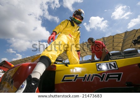 SEPANG, MALAYSIA - NOVEMBER 22 :  Driver Ho Pin Tung of A1 Team China exits his car after qualifying  session at A1GP World Cup of Motorsport in Sepang, Malaysia November 22, 2008.
