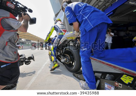 SEPANG, MALAYSIA - OCT 23 : A mechanic pushes Italian Valentino Rossi's bike during the first testing session at Shell Advance Malaysian Motorcycle Grand Prix held October 23, 2009 in Sepang, Malaysia.
