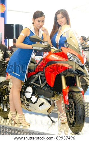 SEPANG, MALAYSIA-OCT 21: A pair of unidentified Malaysian models in action during the promotion of Shell Advance at the Malaysian Motorcycle Grand Prix 2011 on October 21, 2011 in Sepang, Malaysia.