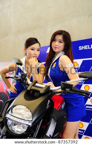 SEPANG, MALAYSIA - OCT 21:A pair of unidentified Malaysian models pose during the promotion of Shell Advance Product at the Malaysian Motorcycle Grand Prix 2011 on Oct 21, 2011 in Sepang, Malaysia.