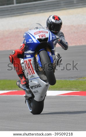 SEPANG, MALAYSIA - OCT 24 : Spanish Jorge Lorenzo of Fiat Yamaha Team does a wheelie after qualifying session at Shell Advance Malaysian Motorcycle Grand Prix on October 24, 2009 in Sepang.