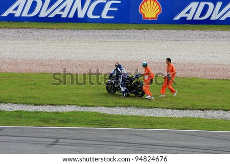 SEPANG, MALAYSIA  OCTOBER 21: Katsuyuki Nakasuga rider from Yamaha Team helped by circuit marshal after crash during MotoGP Test Day at Sepang Circuit, Malaysia on October 21, 2011 in Sepang, Malaysia