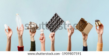 Separate collection of garbage. Human hands holding plastic, glass, metal, paper, lightbulb stuff for recycle. Eco friendly people. Human's hand holds recyclable waste on blue background. Zero waste Foto stock ©