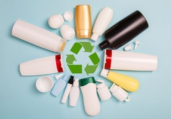 separate collection of sorted HDPE bottles from cosmetics for recycling in for of circle. High-Density Polyethylene recyclable cosmetics package on blue background. Plastic garbage. Save the planet