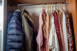 Separation of the wardrobe for summer and winter. Clothes on hangers in dark and light colors