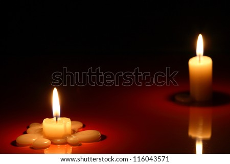 Separation. Two lighting candles on dark background with reflection