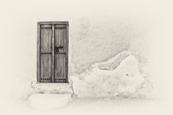 Sepia image of a traditional Arabian carved wooden door with a step in a crumbling plaster wall of a restored house in the Arabian Gulf.