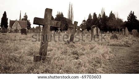 Sepia image of an old cemetary in Suffolk, UK; focus on near gravestone with shallow depth of field