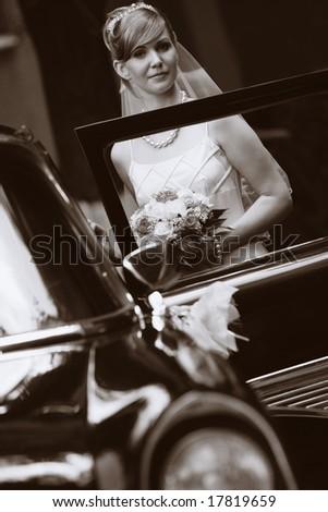 Sepia image of bride standing aside luxury wedding car