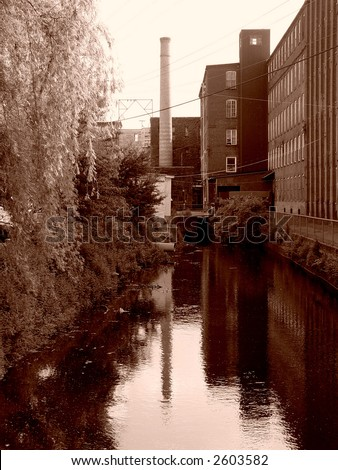 sepia image of canal behind old factory building in easthampton massachusetts, on the left is a bank of trees, on the right a bank of factory windows, in the center a smoke stack