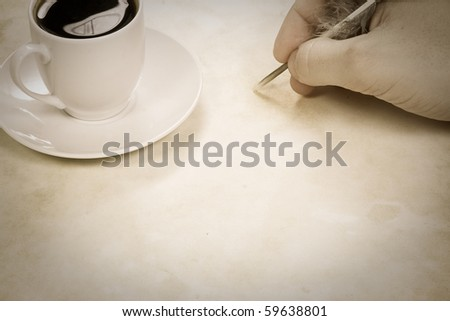 sepia image of coffee and writing hand