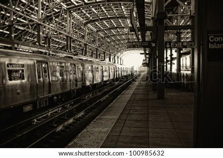 Sepia image of train and platform at the Coney Island subway station
