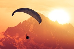 Sepia paraglide silhouette over Alps peaks
