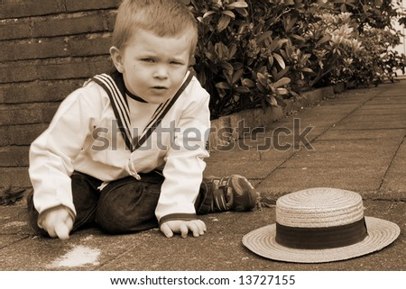 Sepia photo of a boy with a straw hat