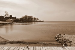 Sepia photo of a wooden pier, platform or marina located next to a sandy beach and a rocky coast full of boulders, stones, and rocks, with a wooden tower and some forest visible in the distance