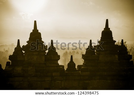 Sepia small stupas on the wall top level of  Borobudur, or Barabudur, temple Jogjakarta, Java, Indonesia at sunrise. It is a 9th-century Mahayana temple and the biggest  Buddhist Temple in Indonesia.