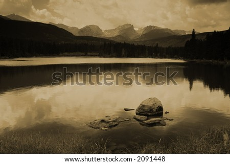 sepia tone vintage style photo of lake, reflection and storm clouds