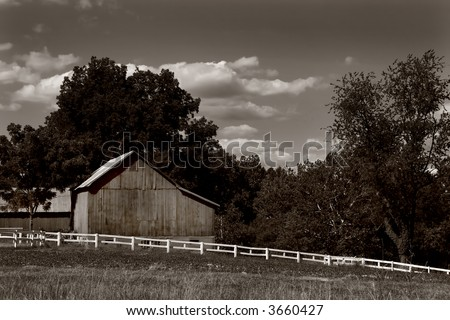 Sepia toned black and white photo of a barn and white fence in Harford County, Maryland