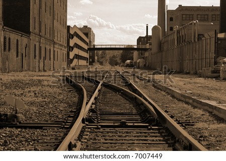 sepia toned image of railroad track switching station converging in the distance in cambridge massachusetts flanked by factory buildings