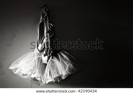 8209ede605f7 sepia toned image of tutu and ballet slippers hanging on wall lit from  sunlight on the