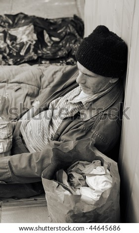 Sepia toned photo of a homeless man on the street, seated, surrounded by his meager belongings.