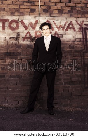 Sepia Toned Photograph Of A Vintage Used Cars Salesman Standing In Business Suit At A Tow Away Area With Old Brick Wall Background