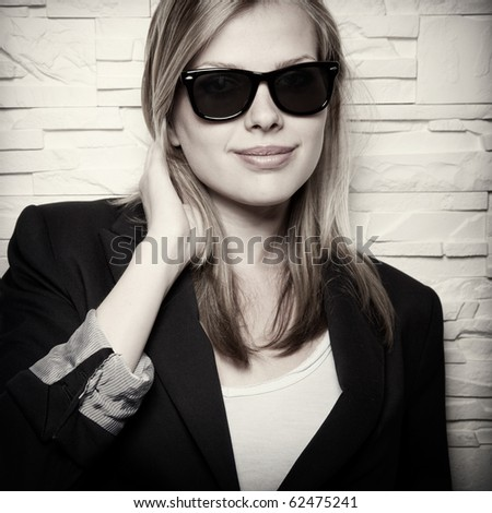 sepia toned portrait of stylish casual girl with sunglasses in front of a wall - stock photo