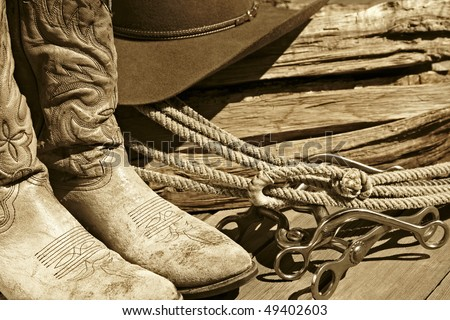 Sepia-toned rustic western image of cowboy boots, cowboy hat, rope, horse bits and stacked wood. - stock photo