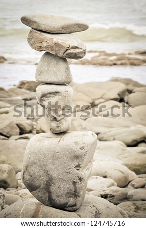 sepia toned stack of balanced rocks on a beach