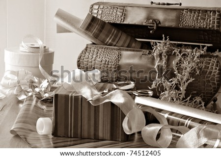 Sepia toned still life of partially wrapped gift with scissors and curling ribbon.  Vintage metal chest with wrapping supplies in soft focus in background.