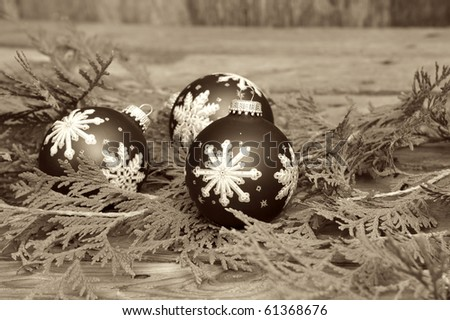 Sepia toned vintage image of three christmas balls and some cedar