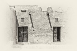 Sepia view of the inner courtyard of a traditional old Arabian adobe house in strong sunlight with shadows from wooden gutters and carved wooden doors and window lattices for ventilation.